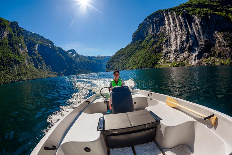 Frau, die einen Motorboot sieben Schwesterwasserfall auf dem Hintergrund fährt lizenzfreie stockbilder