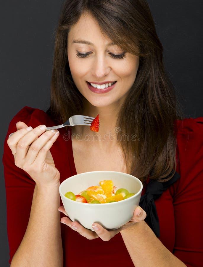 Frau, die einen Obstsalat isst lizenzfreie stockfotografie
