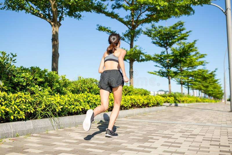Frau, die in einen Park läuft stockfoto