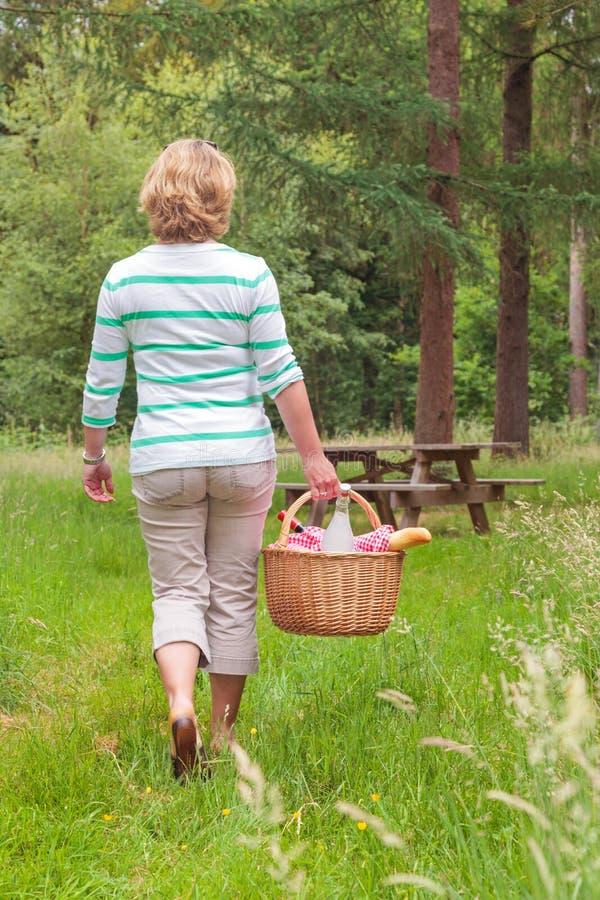 Frau, die einen Picknickkorb trägt lizenzfreie stockfotos