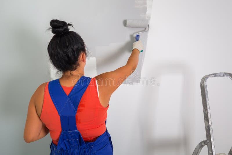 Frau, die einen Raum malt lizenzfreies stockbild