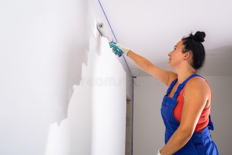 Frau, die einen Raum malt lizenzfreie stockfotos