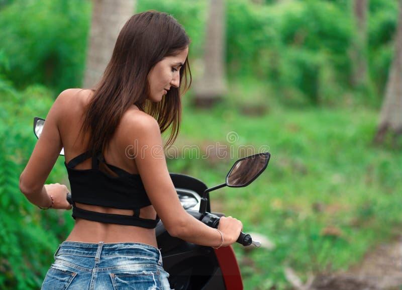 Frau, die einen Roller schaut im Seitenspiegel f?hrt Abschluss oben stockfoto