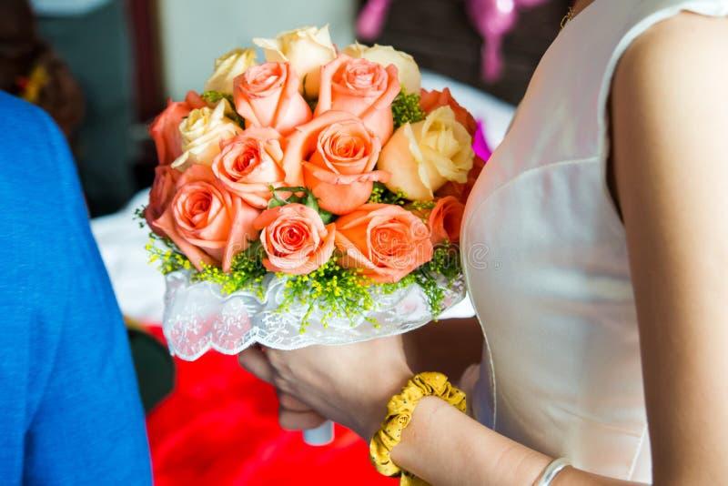 Frau, die einen Rosenblumenstraußabschluß hochhält stockbild