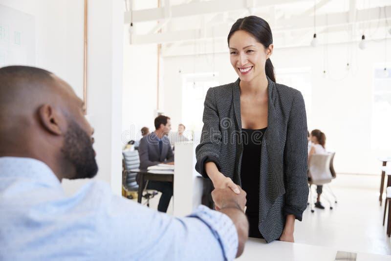 Frau, die einen schwarzen Geschäftsmann bei einer Bürositzung grüßt stockbilder