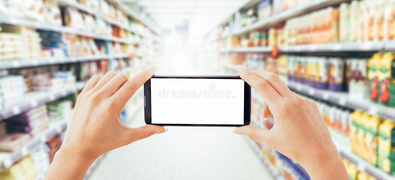 Frau, die einen Smartphone am Supermarkt verwendet stockfoto