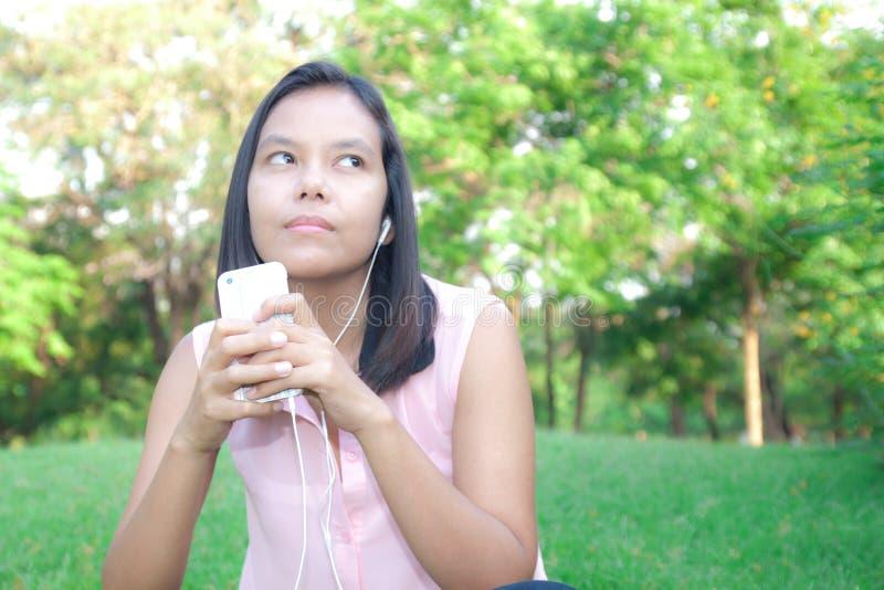 Frau, die einen Smartphone verwendet, um Musik beim Sitzen zu hören in einem p stockbild