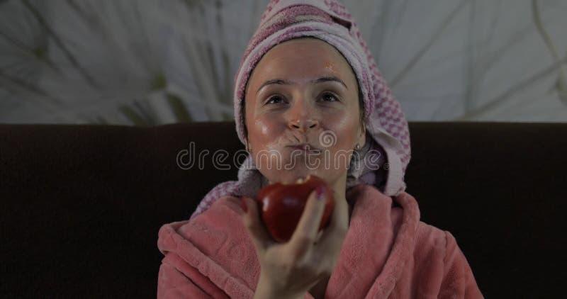 Frau, die einen Sp?t- Film an Fernsehen, einen Apfel essend aufpasst Bademantel, Gesichtsmaske stockfoto