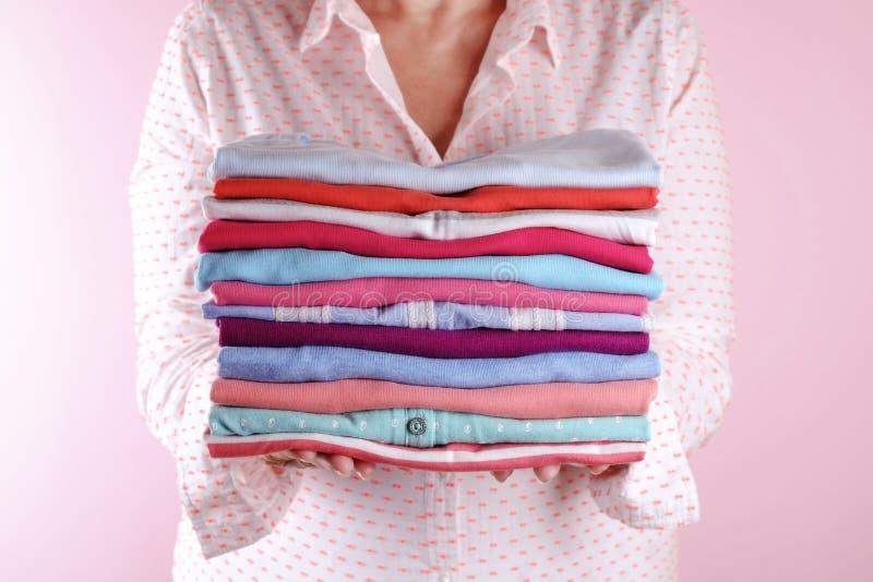 Frau, die einen Stapel der gefalteten Kleidung, Unisex für Mann u. Frau, unterschiedliche Farbe u. Material hält Reisevorbereitun stockfoto