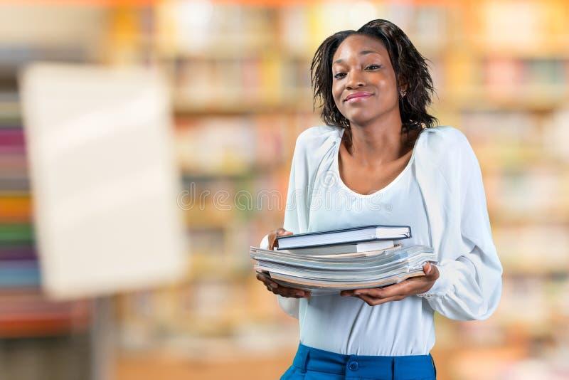 Frau, die einen Stapel von Büchern hält stockbild