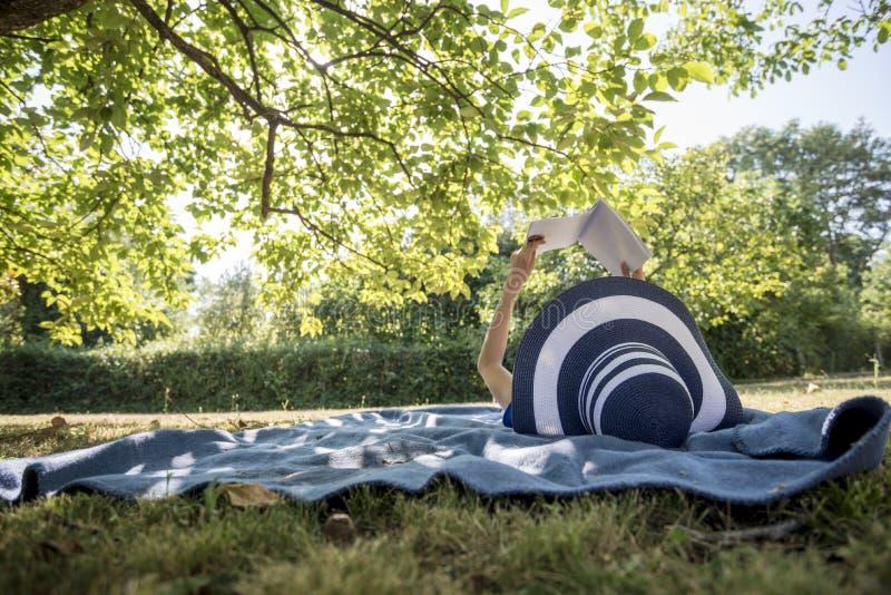 Frau, die einen Strohhut in der Sommernatur liest ein Buch trägt lizenzfreie stockfotos