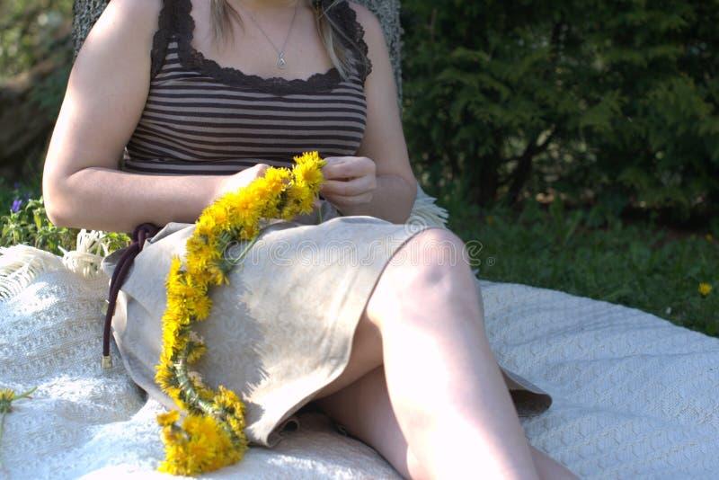 Frau, die einen traditionellen Kranz des Löwenzahns twining ist stockfoto