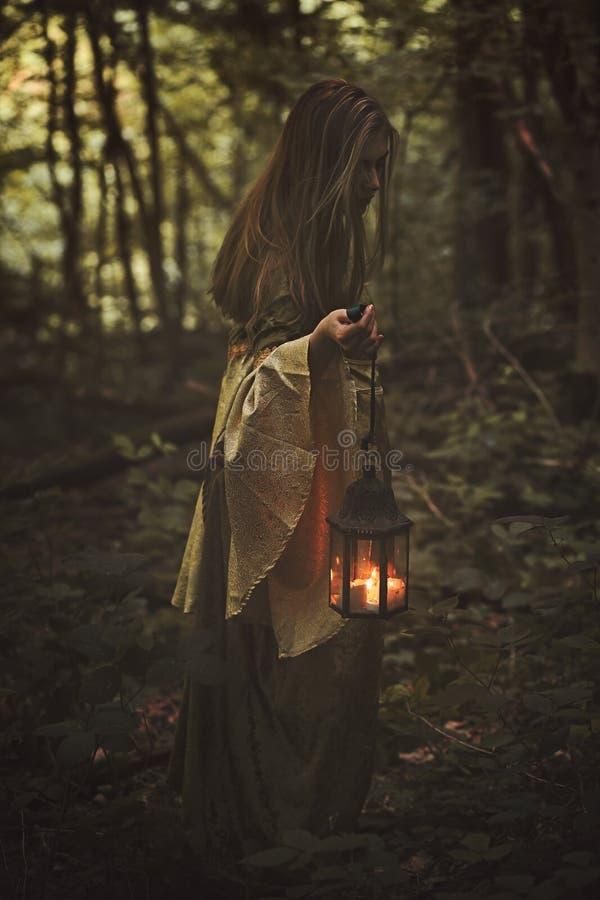 Frau, die in einen Wald mit Laterne geht lizenzfreie stockbilder