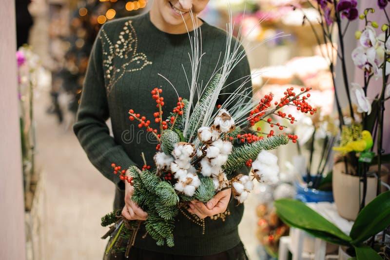 Frau, die einen Winter Weihnachtsblumenstrauß gemacht vom Tannenbaum, -baumwolle und -beeren hält lizenzfreie stockfotografie