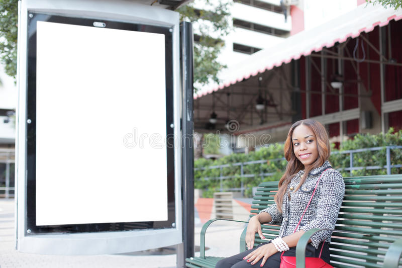 Frau, die an einer Bushaltestellebank sitzt lizenzfreies stockfoto