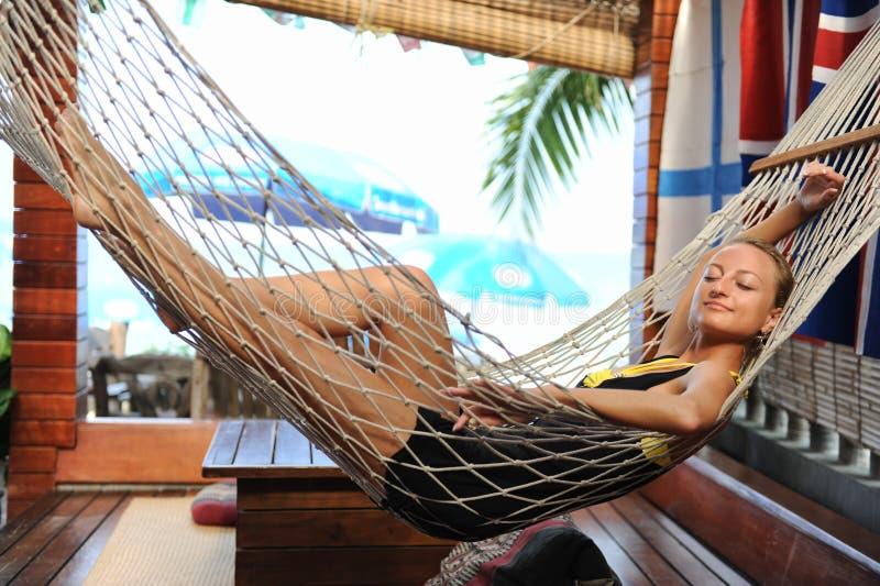 Frau, die in einer Hängematte sich entspannt stockfotografie