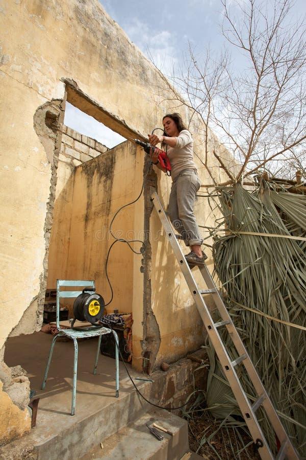 Frau, die an einer Leiter mit einem Bohrer arbeitet und steht lizenzfreie stockfotos