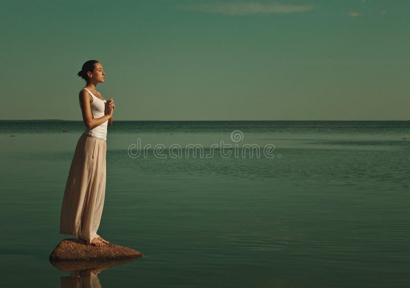 Frau, die in einer Yogahaltung meditiert stockfotografie