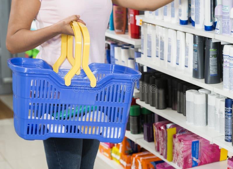 Frau, die Einkaufskorb in der Apotheke hält stockbilder