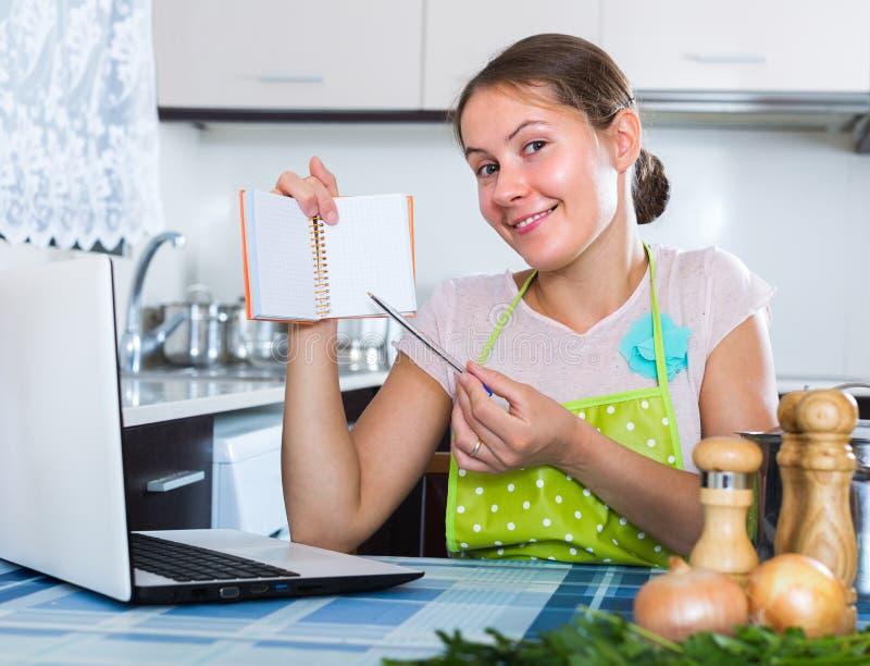 Frau, die Einkaufsliste an der Küche macht stockfotos