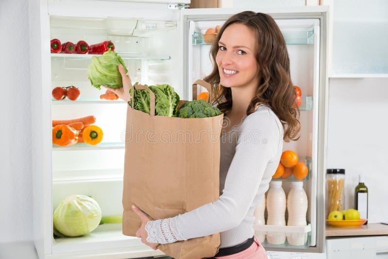 Frau, die Einkaufstasche mit Gemüse hält stockfotografie