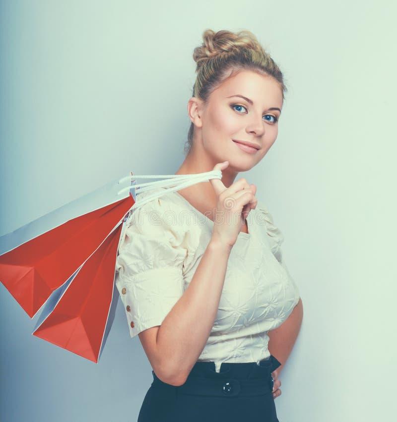 Frau, die Einkaufstaschen gegen einen grauen Hintergrund hält lizenzfreies stockbild