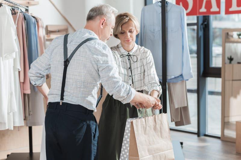 Frau, die Einkaufstaschen gibt, um zu bemannen stockfoto