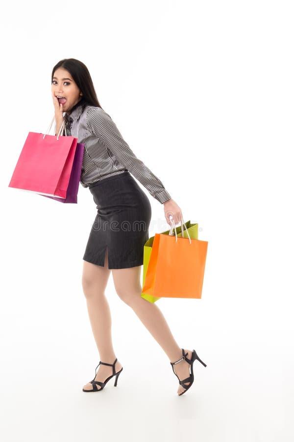 Frau, die Einkaufstaschen mit Klatsch und überraschendem Gesichtsausdruck hält stockfoto