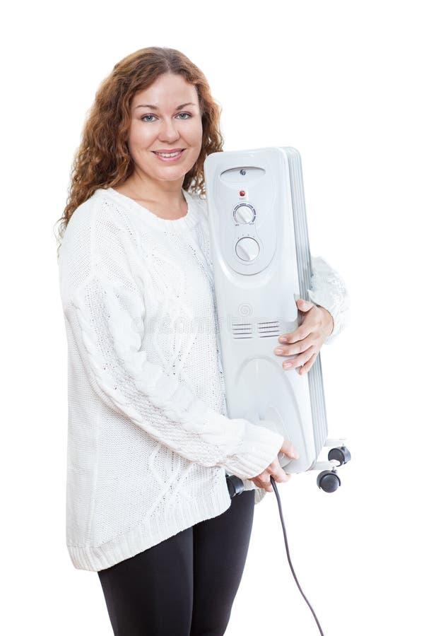 Frau, die elektrischen Ölheizkörper in den Händen lokalisiert auf weißem Hintergrund hält lizenzfreie stockfotografie