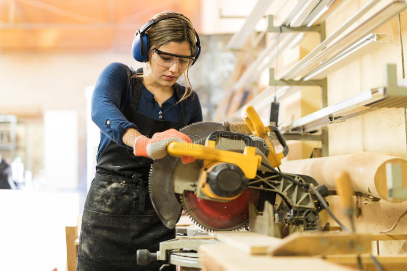 Frau, die Elektrowerkzeuge in einem woodshop verwendet stockfotografie
