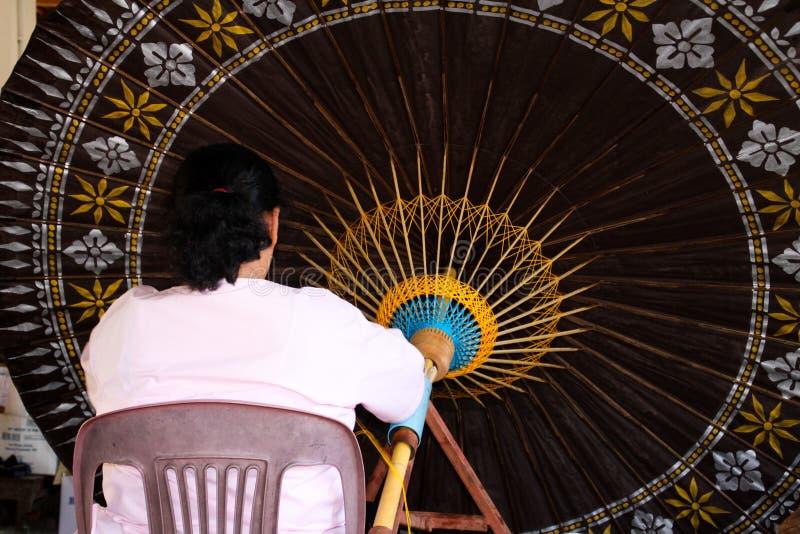 Frau, die an enormem Papierregenschirm in Chiang Mai, Thailand arbeitet lizenzfreies stockbild