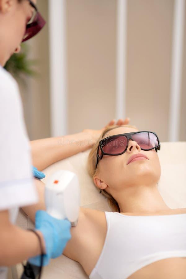 Frau, die enthaarenden Salon besucht und Laser-Enthaarung genie?t lizenzfreies stockfoto
