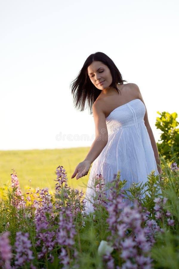 Frau, die entlang das Feld geht lizenzfreie stockbilder