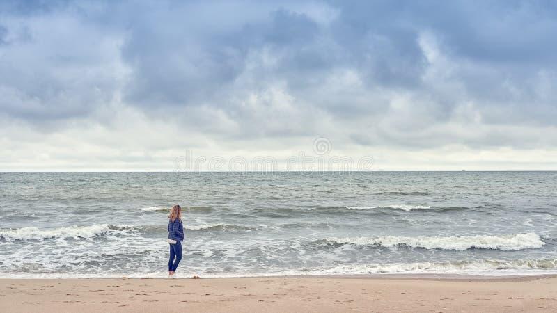 Frau, die entlang den Rand der Brandung auf einem Strand geht stockfotografie