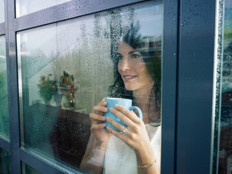 Frau, die entlang des Fensters anstarrt stockfotografie