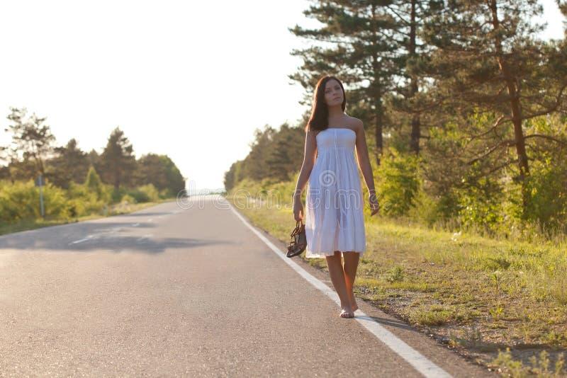 Frau, die entlang die Straße geht stockfotos