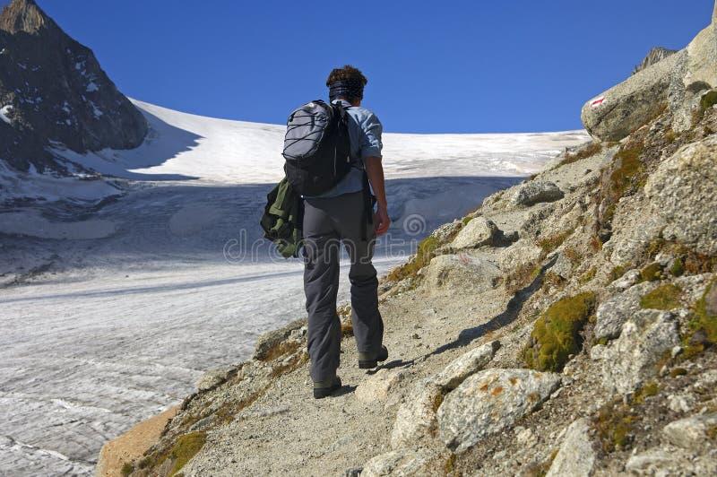Frau, die entlang einem Gletscher wandert lizenzfreie stockfotografie