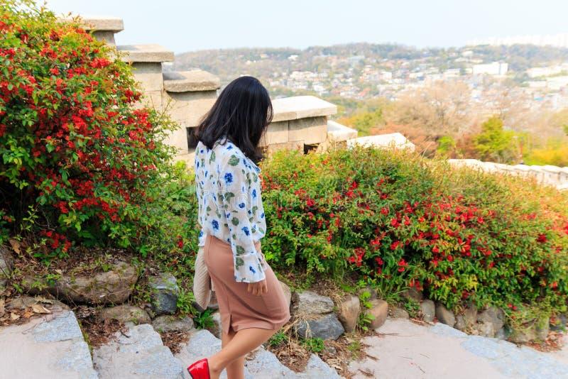 Frau, die entlang die Seoul-Stadtmauer geht stockbild