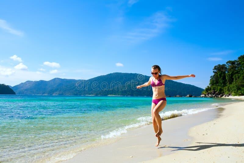 Frau, die entlang tropischen Inselstrand läuft lizenzfreie stockfotos