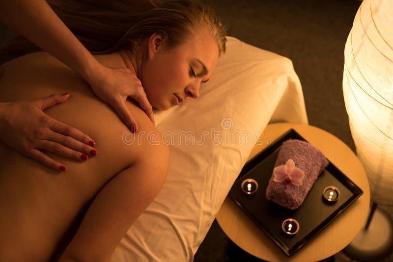 Frau, die entspannende Rückenmassage in der kosmetischen Badekurortmitte in s genießt stockfoto