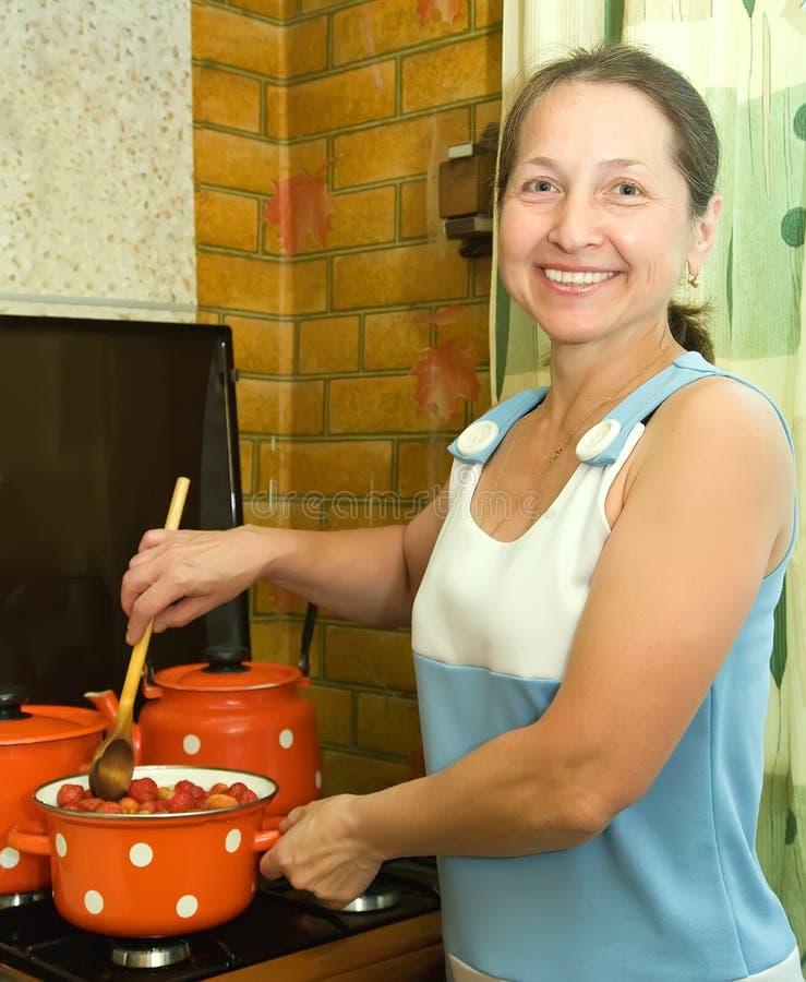 Frau, die Erdbeeremarmelade konserviert lizenzfreie stockbilder