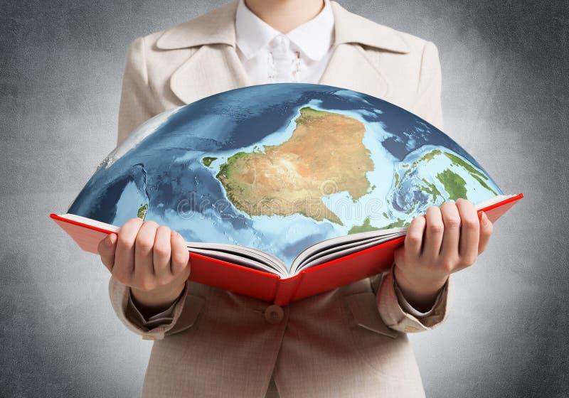 Frau, die Erdkugel im offenen Buch zeigt stock abbildung