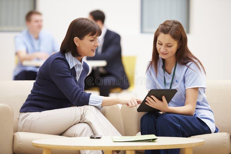 Frau, die Ergebnisse mit Krankenschwester On Digital Tablet bespricht stockbild