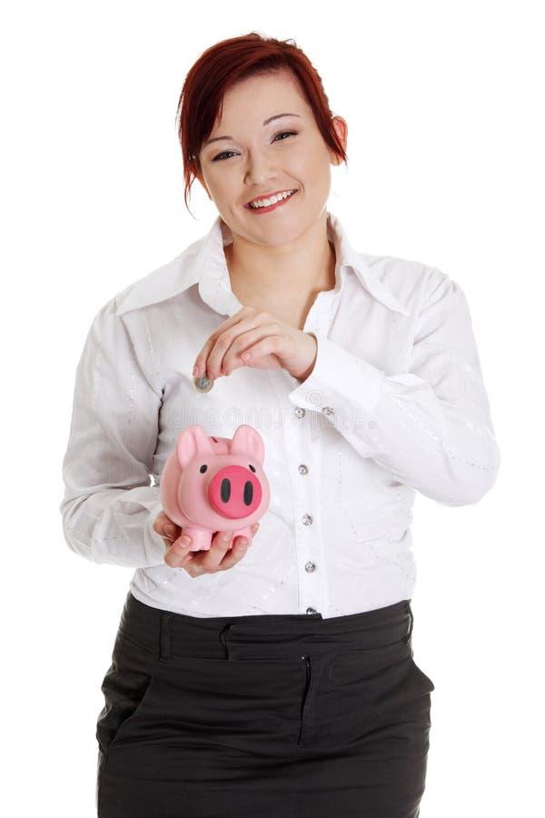 Frau, die Euromünze in piggy Querneigung einsetzt. stockbild