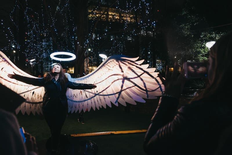 Frau, die für Foto im Winter-Lichtfestival in Canary Wharf, London, Großbritannien aufwirft stockbild