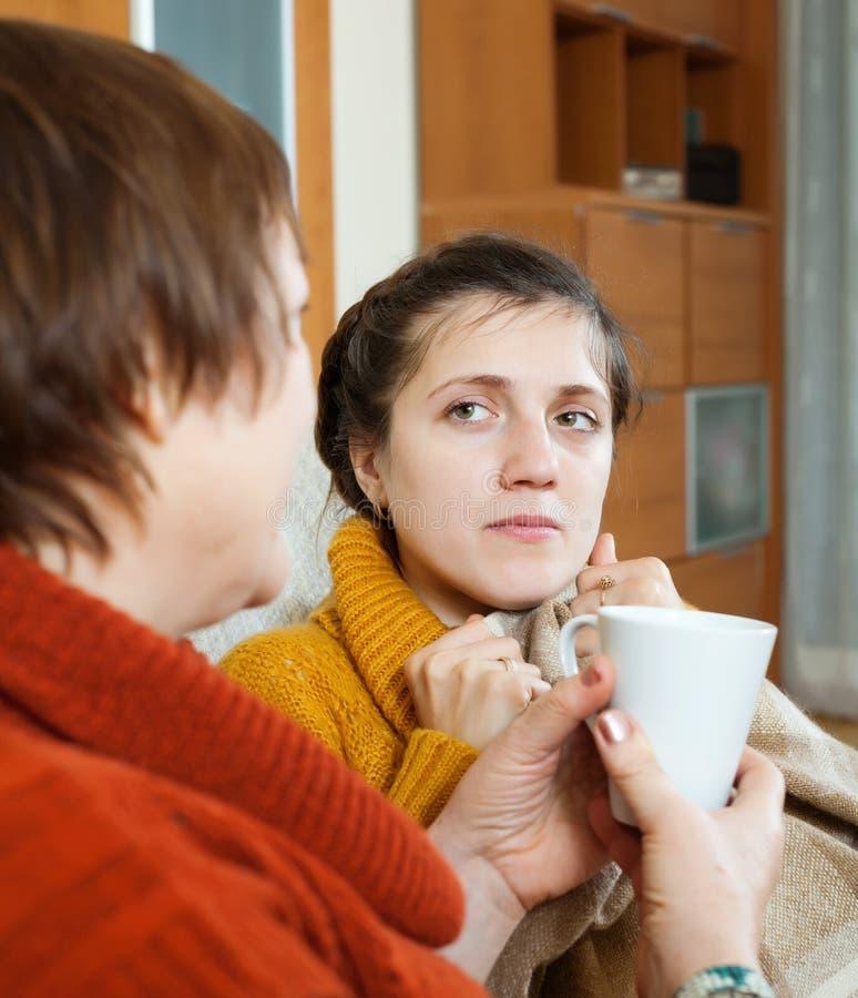 Frau, die für kranke erwachsene Tochter sich interessiert stockfoto