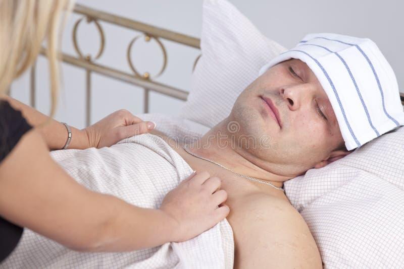Frau, die für kranken Mann sich interessiert stockbild