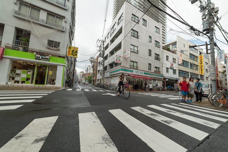 Frau, die Fahrrad über dem Fußgängerübergang hält ihr Telefon fährt lizenzfreies stockfoto