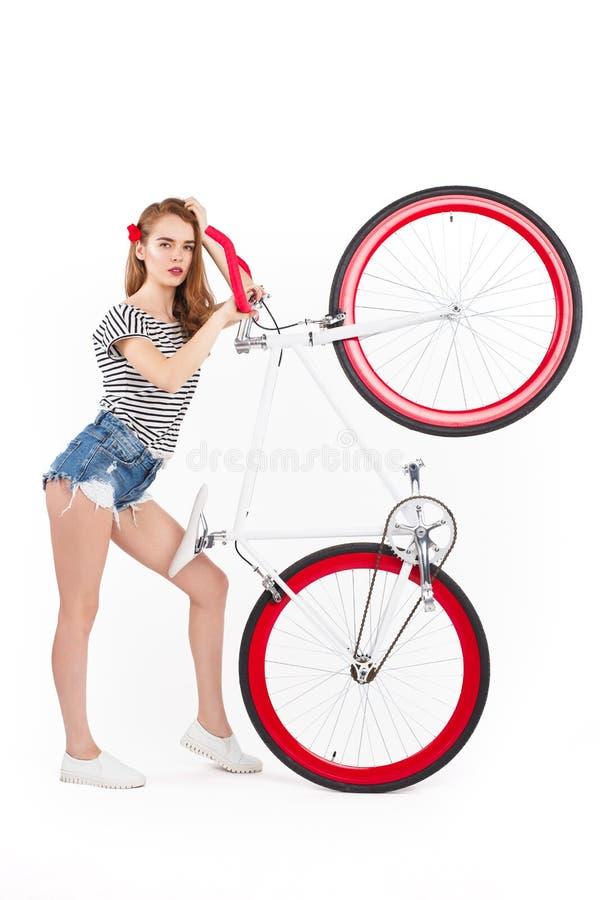 Frau, die Fahrrad hochhält lizenzfreies stockfoto