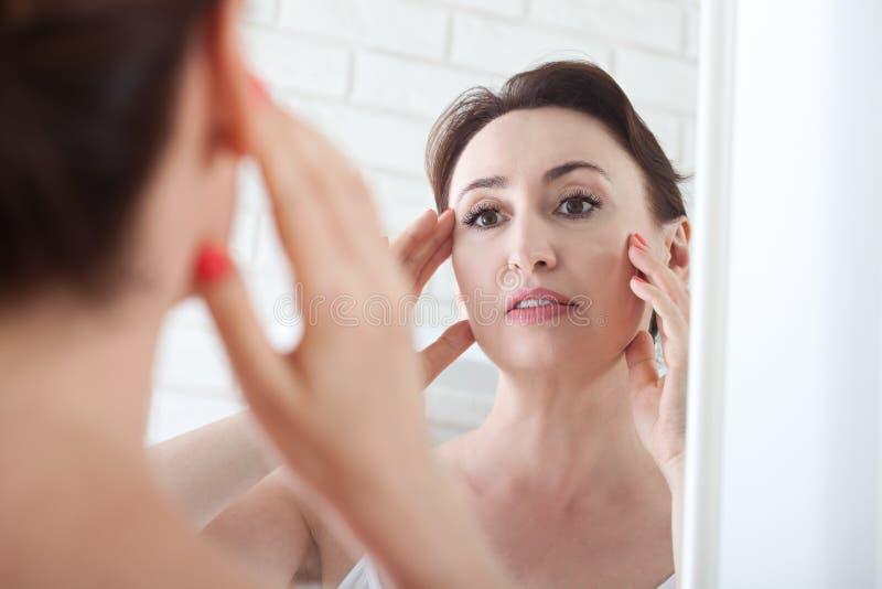 Frau, die Falten im Spiegel betrachtet Plastische Chirurgie und Collage stockbild